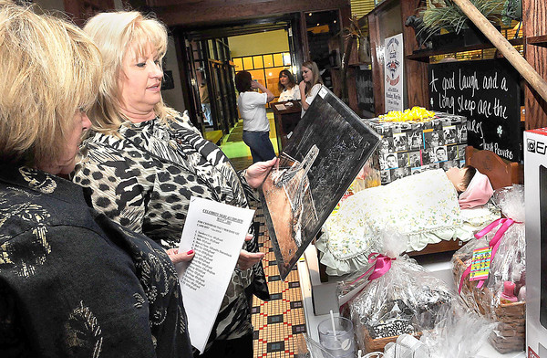 F. BRIAN FERGUSON/THE REGISTER-HERALD=Vickie Cole, owner of Boston Beanery, left, and Kathy Housh, Crossroads Mall General Manager, right, Read over the Celebrity Night Auction Items during Monday's Celebrity Night event.