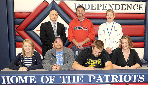 Independence's Zach Tucher signs to play college football on Tuesday afternoon at the school. (Left to right, front) Sister, Taylor Tucker, Father, Lee Tucker, Zach Tucker, and Mother Heather Tucker, (rear left to right), Assistant Principal Rick Shupe, Athletic Director Rick Vass, and Principal Chris Perkins.. F. Brian Ferguson/The Register-Herald