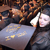 Sandra Smith, right, of Beckley, looks at Angela Robinson, of Rainelle, cap during New River Community & Technical College commencement ceremony held at the Chuck Mathena Center in Princeton.<br /> Rick Barbero/The Register-Herald