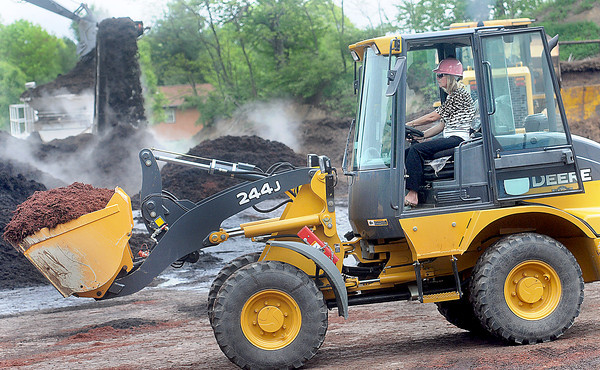 Margaret Ann O'Neal puts her public relation skills to work as she moves a load of mulch during a Monday press conference at Control Products Inc. in Daniels as part of the United Way and Mulch for a Month. F. Brian Ferguson/The Register-Herald