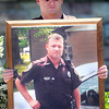 "Beckley Police Sgt. David Allard holds a photo of fellow, fallen officer Chuck Smith as area law enforcement gathered in front of the Fayette County Courthouse on Wednesday for the FOP""s Annual Police Memorial Service.F. Brian Ferguson/The Register Herald"