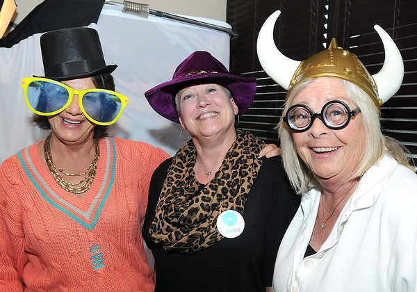 Lisa Mohler, of Daniels, left, Patricia Bailey, director Women's Resorce Center and Marcy Nolan, of Daniels, have fun with props used for the photo booth that was set up at The Dish Cafe in Daniels, during Celebrity Night.<br /> Rick Barbero/The Register-Herald