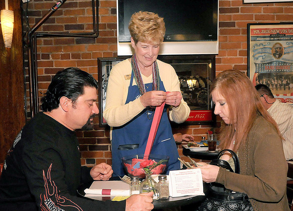 F. BRIAN FERGUSON/THE REGISTER-HERALD=Joe Mortaro, left, and Tammy Wilson, right, buy some auction tickets from City National's Abigail Scott at Fosters during Monday's Celebrity Night event.