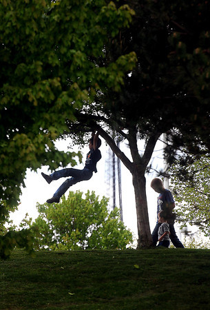 Levi Dover, 7, left, enjoys being a kid as his brothers Adam 12, and Zach, 2, look on , as he climbs a tree near Tamarack F. Brian Ferguson/The Register-Herald