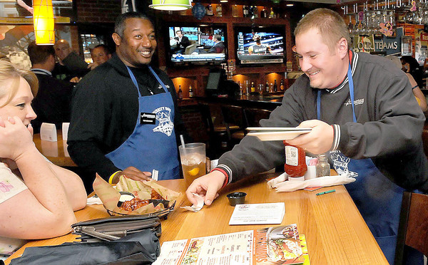 F. BRIAN FERGUSON/THE REGISTER-HERALD=Raleigh General's Brenda Carter, left, is served by Crossroads Chevy's Tim Newsom, center, and her husband Greg Carter,also of Crossroads Chevy, right, at Applebees during Monday's Celebrity Night event.