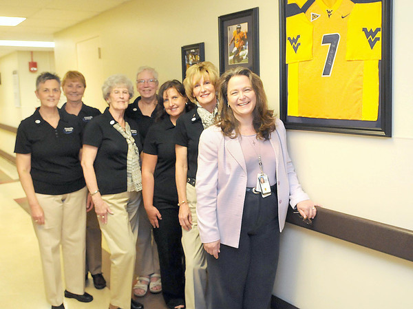 F. BRIAN FERGUSON/THE REGISTER-HERALD=The Friends of Coal Ladies Auxiliary members, (from left). Helga Gulley, Nancy Gentry, Judy Bays, Carol Roles, Nancy Paugh, Regina Fairchild, and Director Karin McGraw display the new sports memoribilia located at the VA.