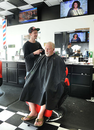 Jared Hall, left, cuts Shay Couch, of Fayetteville, hair at the Country Shop and Salon in Fayetteville.<br /> Rick Barbero/The Register-Herald