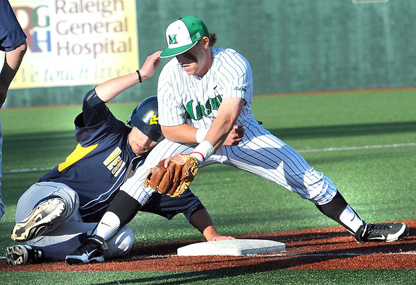 Chris Rasky, left, of WVU slides save into third base under the tag of Aaron Bossi, of Marshall during the game at Linda K. Epling stadium in Beckley Tuesday night.<br /> Rick Barbero/The Register-Herald