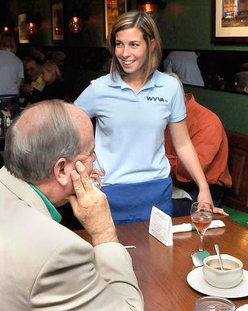 F. BRIAN FERGUSON/THE REGISTER-HERALD=Beckley Mayor Emmett Pugh, left, hears the specials from WVVA's Jamie Baker, right, at Mcbees during Monday's Celebrity Night event.