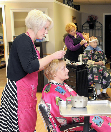 Rootz Salon Owners Miranda Edwards-Sargent, front and Mother, Brenda Edwards, rear, work on clients at their new location in Sophia.  F. Brian Ferguson/The Register-Herald