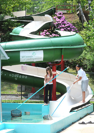 Kristin Dugvid, left, and Karmella Wynne, both lifeguards at New River Park pool, clean debris from the waterslide. Pool will open this weekend. Hours will be Saturday, 10 am to p.m., Sunday, 1p.m. to 6 p.m., and Monday thru Friday, 12 to 6. <br /> Rick Barbero/The Register-Herald