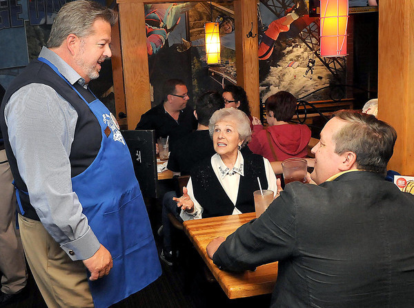 F. BRIAN FERGUSON/THE REGISTER-HERALD=Chuck Turner of Jim Lively Insurance's Beckley Office, left, tends to his bosse's table as Jim Lively Insurance Owners Loretta Lively, center, and oldest son Jim Lively Jr., right, both of Oak Hill, enjoy the meal at Applebees during Monday's Celebrity Night event.