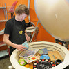 Auggie Graff, floor staff at the Pottery Place at Galleria Plaza in Beckley gets ready to fire items in the kiln.<br /> Rick Barbero/The Register-Herald