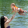 "April Hood, of Beckley, shows her 5 month-old son Vincent Rosas what summer is all about on Thursday afternoon on the beach at Lake Stevens. This weekend lake Stevens looks to be packed as it plays host to ""Beach Blast"". F. Brian Ferguson"