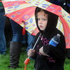 Danielle Cole, 5, of Shady Spring tries to stay dry during a passing Shower at Saturday's Sweet Sweet Treats Dessert Festival at Word Park. F. Brian Ferguson/The Register Herald