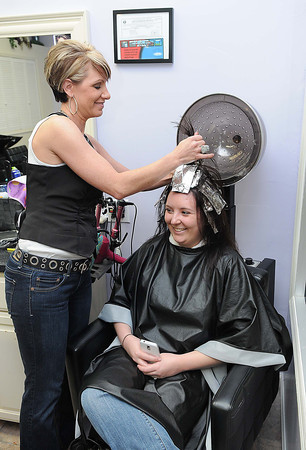Rebecca Duncan, left, works on Rachel Johnson, of Oak Hill, hair at the Country Shop and Salon in Fayetteville.<br /> Rick Barbero/The Register-Herald