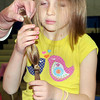 F. BRIAN FERGUSON/THE REGISTER-HERALD=Regan Harrell, 6, of Ansted takes one last look at the 11 inches of her hair that she had cut off to donate to Locks of Love on Saturday at Ansted Middle School.