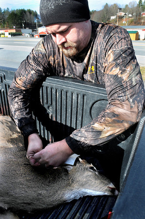 John Hill, of Wyoming County, checks in his deer at the Wildlife Checking Station at the D&D Express Mart in Lester on Monday morning. Hill, who braved below freezing conditions on the first day of gun season, got his spike in Summers County. F. Brian Ferguson/The Register-Herald