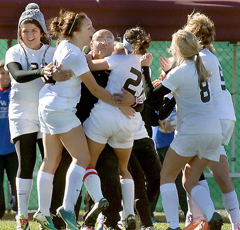 Sissonville's Head Coach Ali Sadeghian, center is mobed by his players seconds after the Lady Indians won the AA/A state Soccer Championship game on Saturday in Beckley. F. Brian Ferguson/The Register-Herald