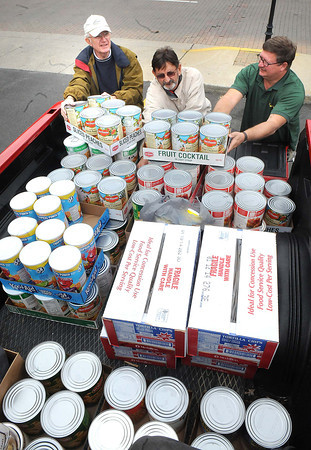 Ron Bratton, left, Lannie Lilly and Gary Walker, with Prosperity First Baptist Church, unload food items the church gather from there food drive and delivered to the Carpenters Corner in Beckley.<br /> Rick Barbero/The Register-Herald