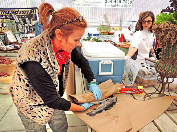 Jennifer Monroe, of Greenbrier Nurseries, packages up a West Virginia Rainbow Trout for purchase at Friday's farmer's market. The locally caught trout was supplied by Mountaineer Trout Farm, located near Coal City.           <br /> Brandi Underwood/The Register-Herald
