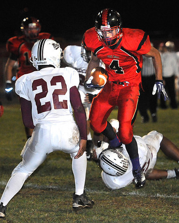 Kadrin Goodman, 4, of Oak Hill, jumps over a Woodrow Wilson defender and scored a touch down during game at Oak Hill High School Friday Night. Mecko Harris, 22, of Woodrow, moves in for a tackle but was to late.<br /> Rick Barbero/The Register-Herald