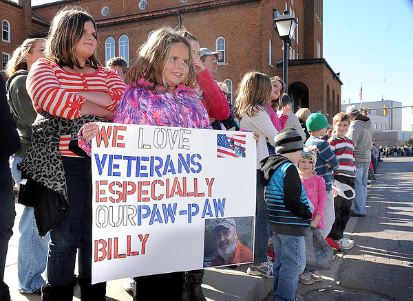 Destiny, 11, left, and Amber Pemberton, 8, daughters of Randy and Tammy Pemberton, of Maple Forf, hold a poster honoring there grandfather Billy Davis during the Beckley Veterans Day Parade on Neville Street uptown Beckley.<br /> Rick Barbero/The Register-Herald