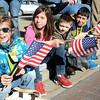 Mya Wooton, 7, left, Abby Wooton, 10, Hunter Elswick and Btyce Wooton, 6, wave americans flags during the Beckley Veterans Day Parade on Neville Street uptown Beckley.<br /> Rick Barbero/The Register-Herald