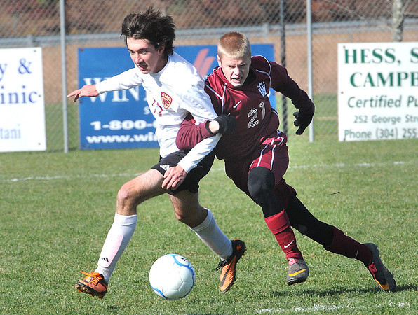 Lanes Butts, left, of Jefferson, and Alex Lewis, of George Washinton, lock arms in the class AAA boys soccer semi-final match held at the YMCA Youth Sports Complex in Beckley Friday morning.<br /> Rick Barbero/The Register-Herald