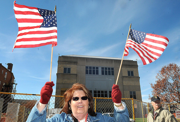 Alicia Lester, of Grandview holds up American flags on Heber Street during the Beckley Veterans Day Parade.<br /> Rick Barbero/The Register-Herald