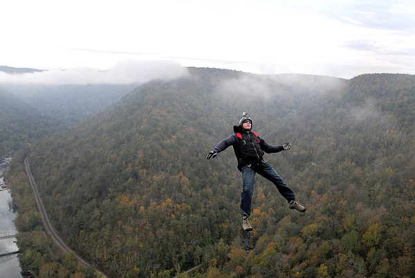 A lone BASE jumper takes the plunge off the New River Gorge Bridge on a foggy Saturday morning during Bridge Day 2013.  F. Brian Ferguson/The Register-Herald