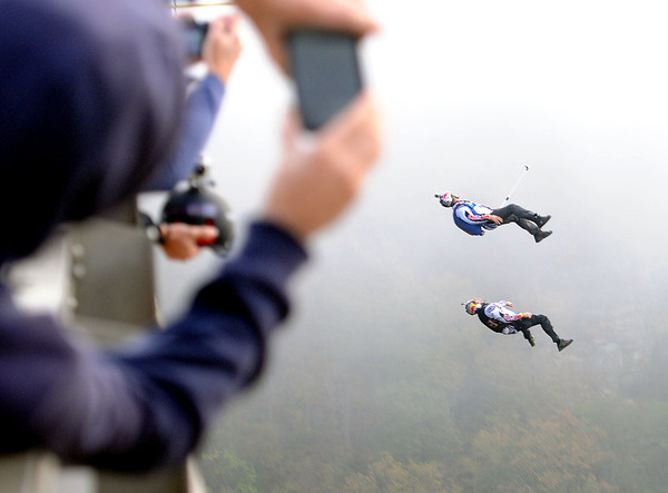 The first two BASE jumpers of Bridge Day 2013 plunged off the New River Gorge Bridge, in tandem, on a foggy Saturday morning.  F. Brian Ferguson/The Register-Herald