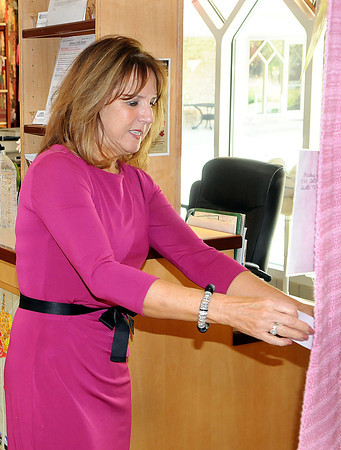 Kay Bess pins a note of support to the longest pink scarf in the world, which was on display at Tamarack, on Tuesday afternoon, to promote breast cancer awareness. F. Brian Ferguson/The Register-Herald