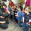 Beckley Fire Fighter, Mark Braskley, left, shows students from Raleigh County Head Start how he looks when he gets all geared up at Beckley Fire Station No. 1 on Third Ave. Beckley Fire Department entertained the students with a tour of the Station for Fire Prevention Week. <br /> Rick Barbero/The Register-Herald
