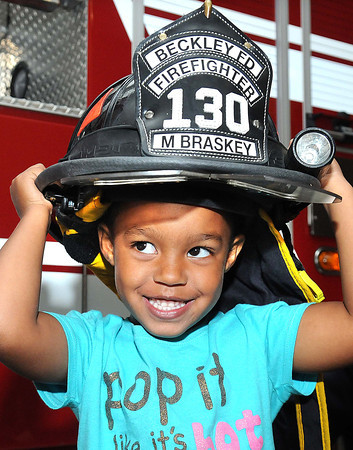 Roslynn Patterson tries on Beckley Fire Fighter, Mark Braskey's hat at Beckley Fire Station No. 1 on Third Ave. Beckley Fire Department entertained kids from the Raleigh County Head Start with a tour of the Station for Fire Prevention Week. <br /> Rick Barbero/The Register-Herald
