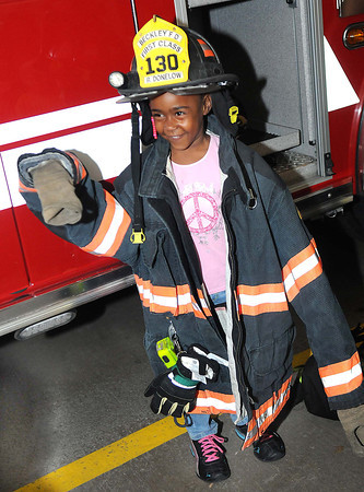 """La""""Niyah Rowe gets suited up in Beckley Fire Fighter, Robert Donelow's gear at Beckley Fire Station No. 1 on Third Ave. Beckley Fire Department entertained kids from the Raleigh County Head Start with a tour of the Station for Fire Prevention Week. <br /> Rick Barbero/The Register-Herald"""