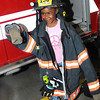 "La""Niyah Rowe gets suited up in Beckley Fire Fighter, Robert Donelow's gear at Beckley Fire Station No. 1 on Third Ave. Beckley Fire Department entertained kids from the Raleigh County Head Start with a tour of the Station for Fire Prevention Week. <br /> Rick Barbero/The Register-Herald"