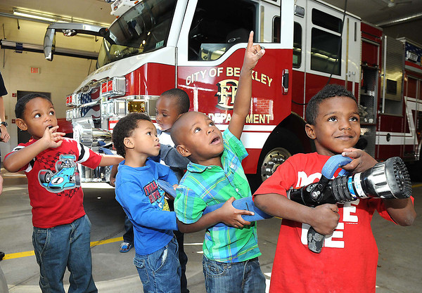 Raleigh County Head Start students, from left, Jacob Mattman, Issac Smith, Xayveon Mtichell, Zymiere Manns and TyRique Davis, play with the fire hose at Beckley Fire Station No. 1 on Third Ave. Beckley Fire Department entertained the kids with a tour of the Station for Fire Prevention Week. <br /> Rick Barbero/The Register-Herald