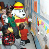 Raleigh County Central Headstart kids gather around Sparky the Fire Dog looking over posters the kids made for a fire safety poster contest.<br /> Rick Barbero/The Register-Herald