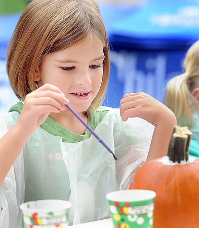 Delaney Meadows, 5, of White Sulpher Springs, enjoys Pumpkin Painting during the Taste of our Town festival in Lewisburg on Saturday. F. Brian Ferguson/The Register-Herald