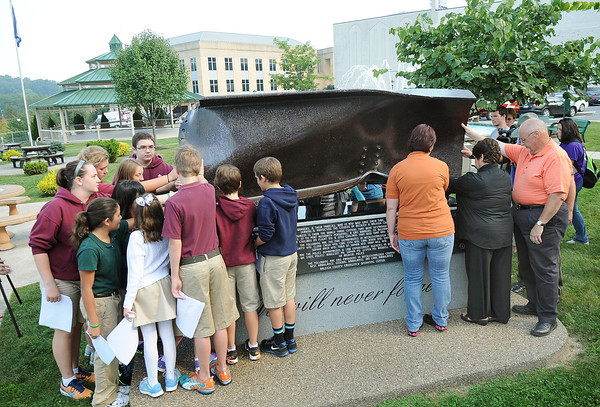 People touch the memorial in Jim Word Memorial Park Wednesday morning during a ceremony honoring 911 victims. <br /> Rick Barbero/The Register-Herald