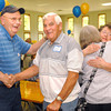 Wayne Anderson SSHS class of 1964 shakes hands with his cousin Glenn Anderson SSHS class of 1949. As their wives Marilyn and Jan Anderson hug in the background at the all class Old School Shady High reunion at the 4-H camp on Saturday, August 31, 2013. Chris Hancock/The Register-Herald