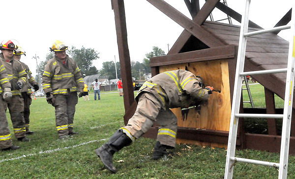 Fayetteville Volunteer Firefighters break through a mock wall in a timed, skill drill during Saturday's Firefighters weekend at the Oak Leaf Festival in Oak Hill. Long is continuing a proud family tradition of firefighting F. Brian Ferguson/The Register-Herald