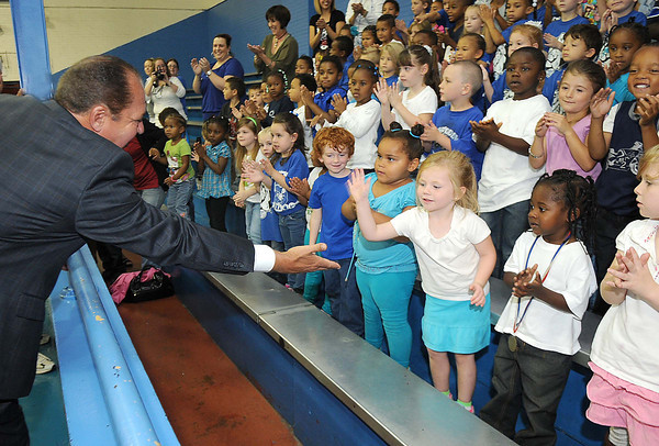 Gov. Earl Ray Tomblin, right, slaps hands with students at Stratton Elementary School. The school recieved a brand new Live Positively TM Fitness Center.<br /> Rick Barbero/The Register-Herald
