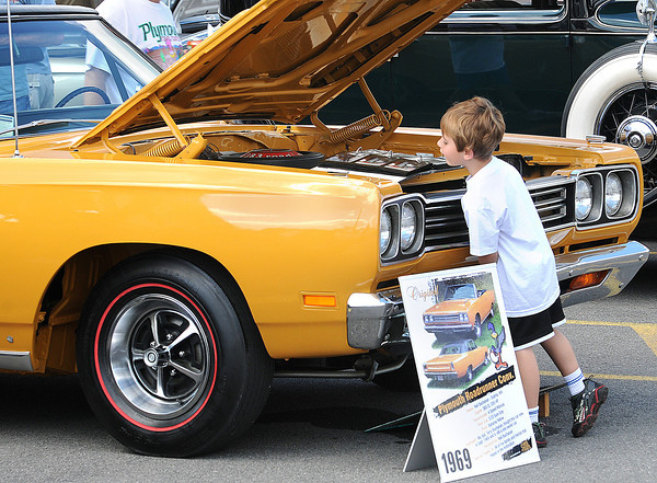 Cody Buchanan, 5, of Sophia, has to get on his tip-toes to look under the hood of a classic 1969 Plymouth Road Runner during Saturday;s 9th Annual Beckley VAMC Motorcycle and Classic Car show at the Beckley VA. F. Brian Ferguson/The Register-Herald