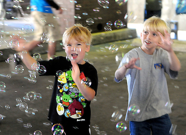 Evan Honaker, 6, of Beckley, left, and C.J. Overbay, 8, of Shady Spring, right, enjoy the bubble machine in the United Bank Arcade during Saturday's Kid's festival in downtown Beckley.. F. Brian Ferguson/The Register-Herald