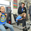 Gov. Earl Ray Tomblin, right, and  Jake Steinfield, chairman of the National Foundation for Governors Fitness Councils, watch Majeedah Canada, left, and Emily Collier, 5th graders at Stratton Elementary School use the schools brand new Live Positively TM Fitness Center.<br /> Rick Barbero/The Register-Herald