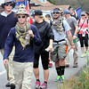 Former United States Marine Chris Senopole, front, walks past his home in Daniels with his fellow supporters on Wednesday afternoon. The group has been walking every day since June 15 to raise awareness and funds in support of the Wounded Warriors. The journey, which started in California, will conclude in Washington D.C.  F. Brian Ferguson/The Register-Herald