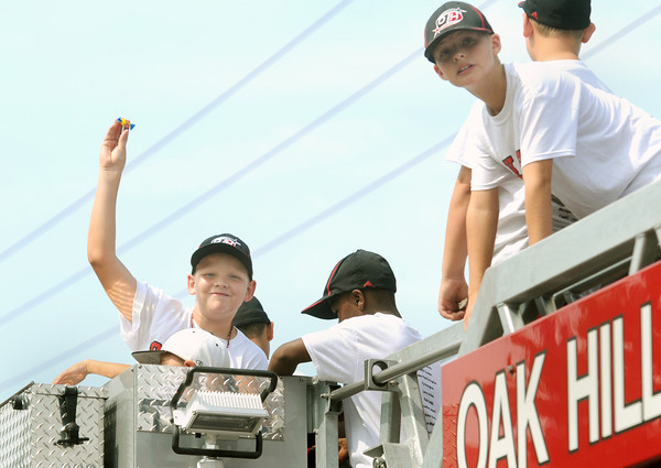 Lane Jordan and his teammates of 9-10 year old Little League All-Star District 4 Champs tosses some candy during Saturday's Parade at Oak Leaf Festival in Oak Hill. Long is continuing a proud family tradition of firefighting F. Brian Ferguson/The Register-Herald