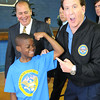 Kaeden Moore, 9, flexes his muscle for Gov. Earl Ray Tomblin, left, and Jake Steinfield, chairman of the National Foundation for Governors Fitness Councils, at Stratton Elementary School. The school recieved a brand new Live Positively TM Fitness Center.<br /> Rick Barbero/The Register-Herald
